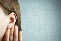 A menina escuta atentamente com sua palma sua orelha, close-up, dentro, o conceito da notícia foto de stock royalty free