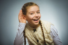 A menina escuta audição da criança algo, mão ao gesto da orelha no fundo cinzento imagem de stock