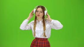A menina escuta a música em fones de ouvido Tela verde video estoque