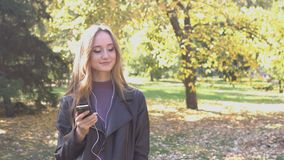 A menina escuta a música no parque vídeos de arquivo