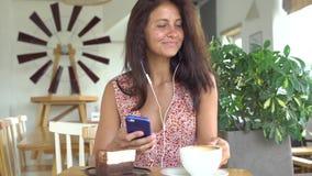A menina escuta a música no smartphone com fones de ouvido filme
