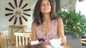 A menina escuta a música no smartphone com fones de ouvido e bebe o café video estoque