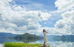 A menina escuta a música que está na plataforma na praia Fotos de Stock Royalty Free