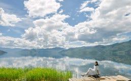A menina escuta a música que senta-se na plataforma na praia Imagens de Stock