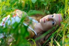 A menina eslavo bonita nova com cabelo longo e vestuário étnico eslavo encontra-se na grama em uma floresta do verão fotos de stock royalty free