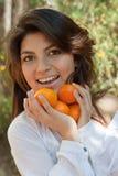 Menina espanhola nova de sorriso com um tangerine Foto de Stock