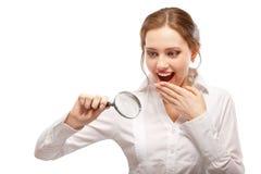 A menina espantada olha através do magnifier Fotos de Stock Royalty Free