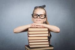 Menina esperta com uma pilha de livros fotografia de stock royalty free