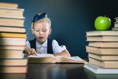 Menina esperta da escola que lê um livro na biblioteca Fotografia de Stock Royalty Free