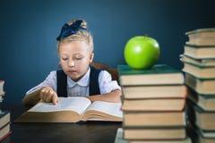 Menina esperta da escola que lê um livro na biblioteca Imagens de Stock