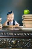 Menina esperta da escola que lê um livro na biblioteca Imagens de Stock Royalty Free