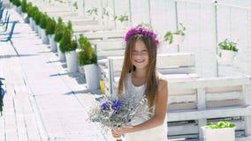 Menina esperta feliz que admira com flores e sorriso lentamente video estoque