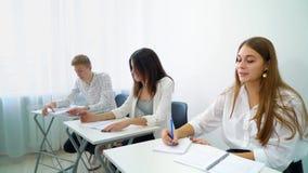 Menina esperta nova da pergunta do mentor de resposta do grupo de estudantes na sala de aula da High School vídeos de arquivo