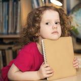 Menina esperta que guardara um livro foto de stock