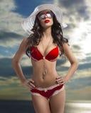 Menina esplêndida no biquini com o chapéu no mar Imagem de Stock