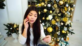A menina esplêndida que fala no telefone e em presentes pedindo, senta-se na árvore e na chaminé decoradas fundo de Natal em bril filme