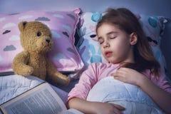 A menina está adormecido na cama fotos de stock royalty free