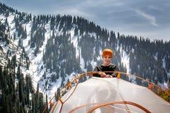 A menina está ajustando uma barraca do turista contra o contexto de uma floresta de montanhas cobertos de neve e de um céu azul c fotografia de stock