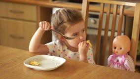 A menina está alimentando a boneca na cozinha Toma o alimento com suas mãos e come-o ela mesma Jogo do ` s da mãe video estoque