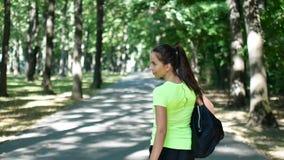 A menina está andando ao longo da alameda para treinar A mulher com saco dos esportes gerencie ao redor in camera e sorri video estoque