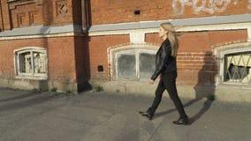 A menina está andando na frente de uma construção vídeos de arquivo
