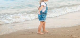 A menina está andando na praia no mar imagem de stock royalty free