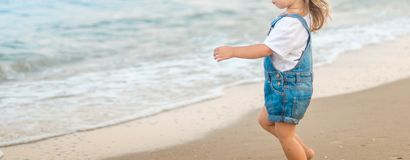 A menina está andando na praia no mar imagem de stock