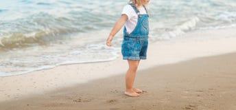 A menina está andando na praia no mar fotos de stock royalty free