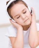 A menina está apreciando a música usando fones de ouvido Fotografia de Stock Royalty Free