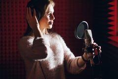 A menina está aprendendo cantar no estúdio da música imagens de stock royalty free