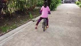 A menina está aprendendo montar uma bicicleta no quintal vídeos de arquivo