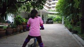 A menina está aprendendo montar uma bicicleta no quintal filme