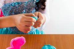 A menina está aprendendo usar a massa colorida do jogo Imagens de Stock
