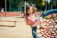 A menina está balançando em um balanço no campo de jogos Imagens de Stock Royalty Free