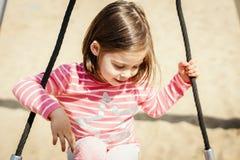 A menina está balançando em um balanço no campo de jogos Imagens de Stock