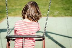 A menina está balançando em um balanço no campo de jogos Fotografia de Stock