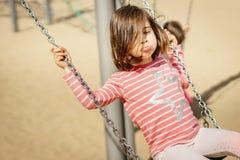 A menina está balançando em um balanço no campo de jogos Fotos de Stock Royalty Free