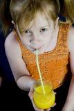A menina está bebendo a laranja Fotografia de Stock