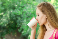 A menina está bebendo o café afastado no parque fotos de stock royalty free