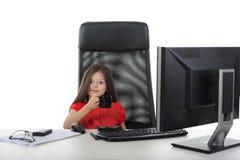 A menina está bebendo o café na frente de um compu Foto de Stock