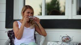 A menina está bebendo o chá no quintal vídeos de arquivo