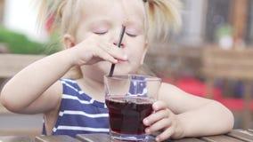 A menina está bebendo o suco em um café vídeos de arquivo