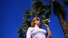 A menina está bebendo uma bebida na rua de um copo descartável contra o céu azul e as palmeiras Vista inferior vídeos de arquivo