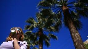 A menina está bebendo uma bebida na rua de um copo descartável contra o céu azul e as palmeiras Vista inferior filme