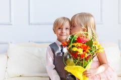 A menina está beijando o menino. imagens de stock