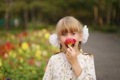A menina está cheirando a flor Fotos de Stock Royalty Free