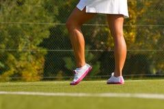 A menina está com a raquete na corte no dia de verão ensolarado Fotografia de Stock