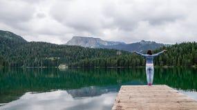 A menina está com suas mãos acima no cais do lago preto no parque nacional Durmitor montenegro Fotografia de Stock
