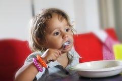 A menina está comendo com uma forquilha fotografia de stock royalty free