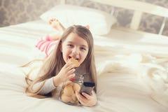 A menina está comendo cookies de farinha de aveia na cama Fotografia de Stock Royalty Free